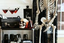 a spooky Halloween bar cart with black glasses, a black chest with drinks, a skull and skeletons around