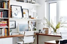 a stylish modern home office nook in white, with a corner desk and a bookcase on one side and a gallery wall on shelves