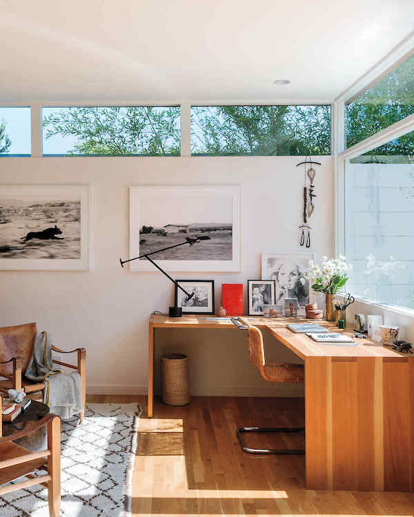 a stylish modern home office with a large corner desk with many artworks and a lovely views of outside
