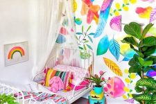 a super bright kid's room with a colorful botanical wall, bright bedding and a rug, colorful mini suitcases and a hot pink planter