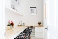 a tiny white home office with a shared corner desk and cabinets under the surface, a large open cabinet and black woven chairs