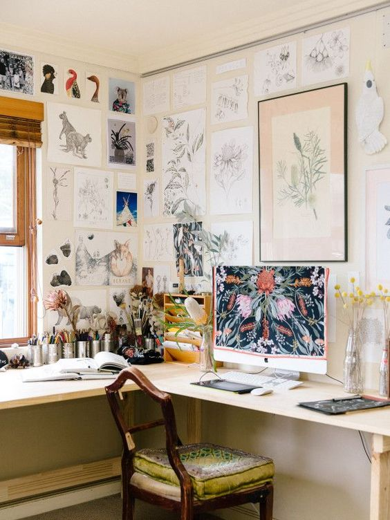 a vintage home office with a corner desk, a vintage chair, a large gallery wall covering the walls and a window