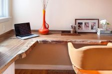 a warm-colored home office with a live edge corner desk, a yellow chair, open shelves and an orange vase