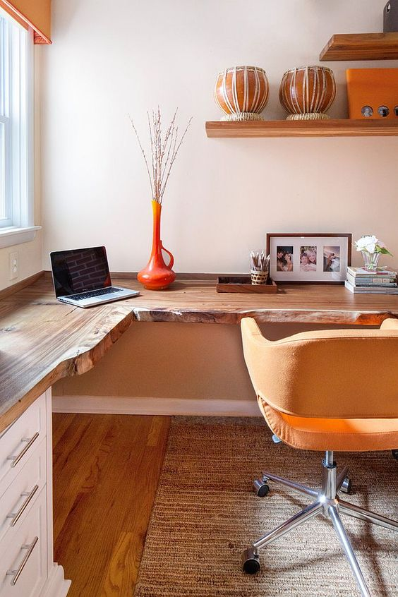 a warm colored home office with a live edge corner desk, a yellow chair, open shelves and an orange vase