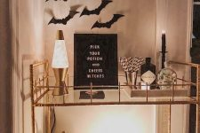 an elegant Halloween bar cart with bats on the wall, lamps and candles, white pumpkins, a sign and a crow