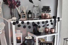 an elegant Halloween bar cart with black and white pumpkins, black dot garlands, copper mugs, bats and dark leaves