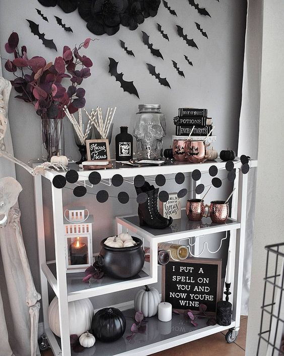 an elegant Halloween bar cart with black and white pumpkins, black dot garlands, copper mugs, bats and dark leaves