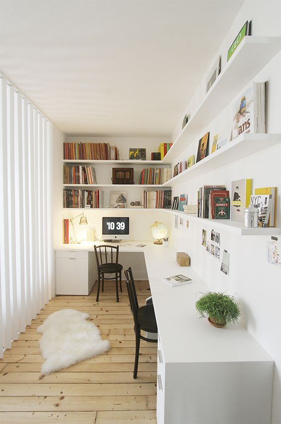 an ethereal Scandinavian home office with a large corner desk, long open corner shelves, faux fur and a glazed wall is wow