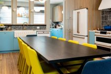 02 The eat-in kitchen shows off blue and white cabinets, a wooden dining table and yellow and navy chairs