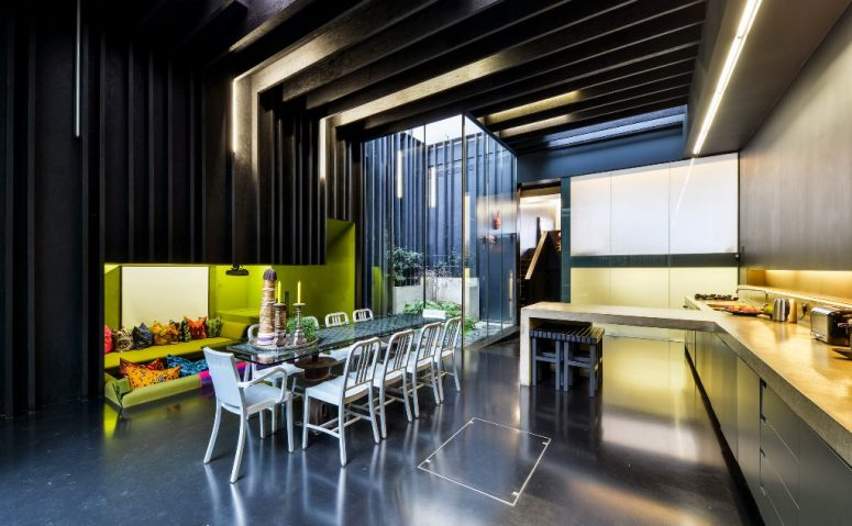 The dining-kitchen zone is done with a sunken conversation pit with lime green walls and bright pillows