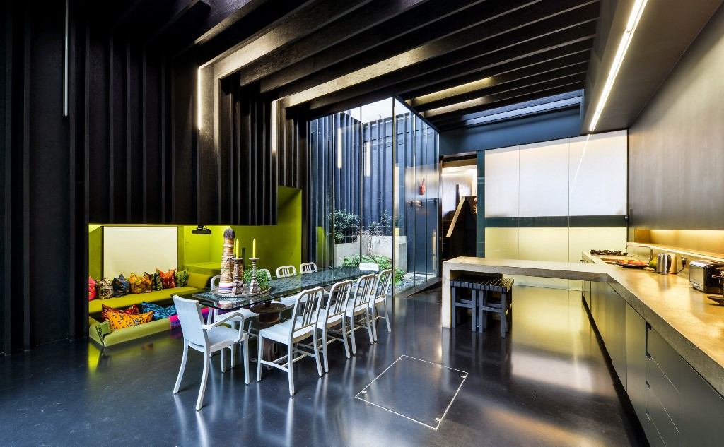 The dining kitchen zone is done with a sunken conversation pit with lime green walls and bright pillows
