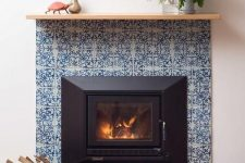 03 a built-in fireplace surrounded with blue printed tiles and navy ones looks ultimately chic and very elegant