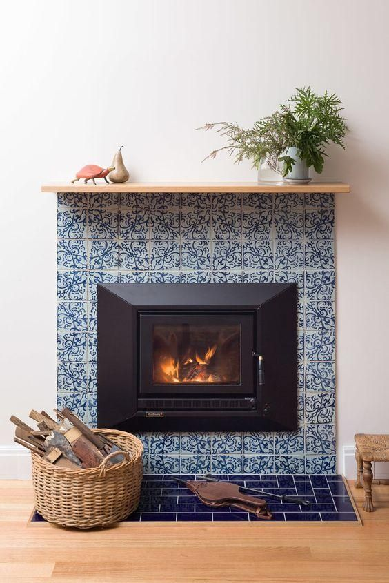 a built-in fireplace surrounded with blue printed tiles and navy ones looks ultimately chic and very elegant
