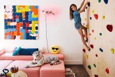 03 a colorful kids' playroom with a climbing wall, pink sofas, colorful artworks and a rug plus toys