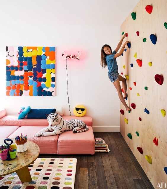 a colorful kids' playroom with a climbing wall, pink sofas, colorful artworks and a rug plus toys