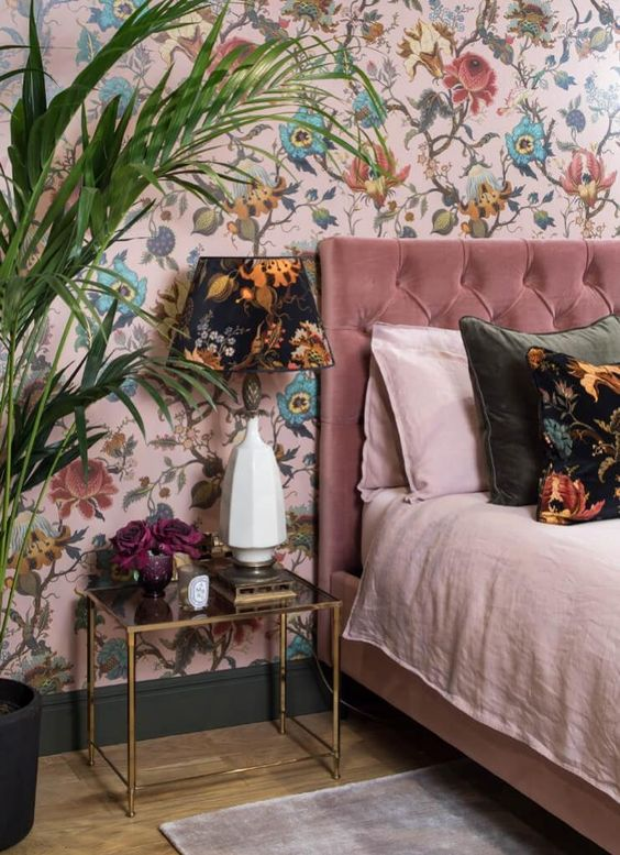 a refined bedroom with a pink floral accent wall and a dark floral table lamp that echoes with it