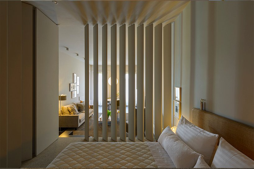 The bedroom is neutral, with white furniture, a large sleek wardrobe and some lamps and artworks