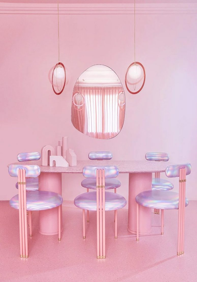 The dining room is done with a pink oval table, iridescent chairs and pendant lamps plus an oddly shaped mirror