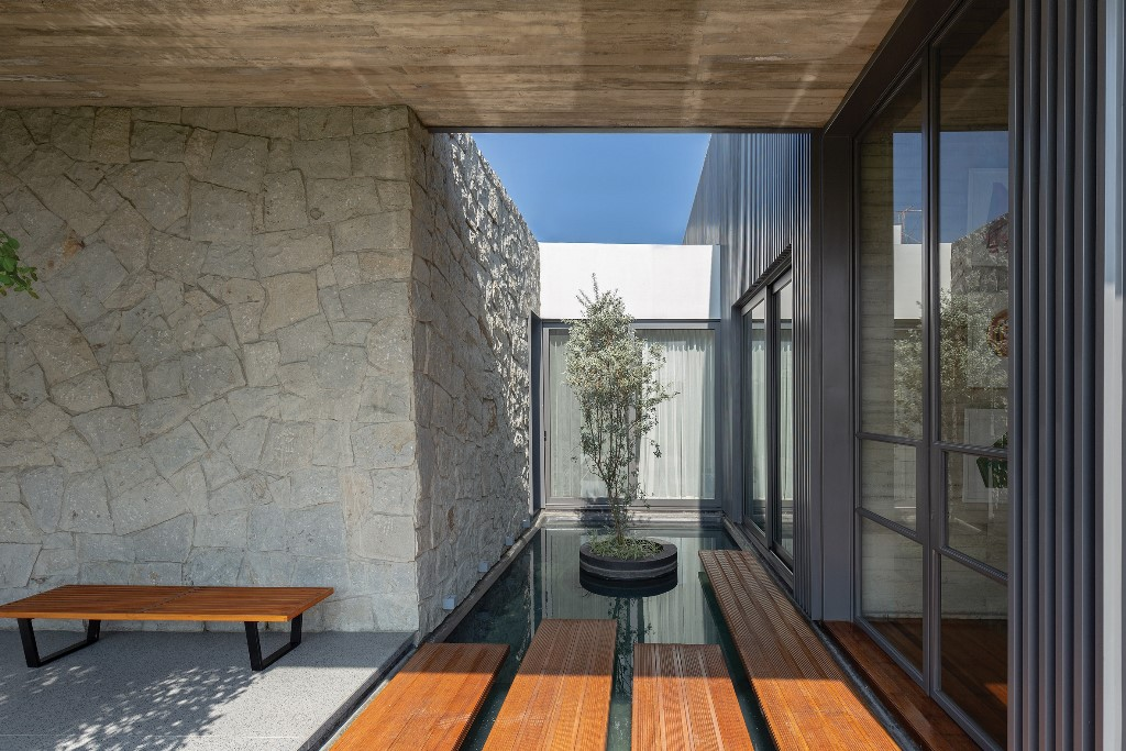 The dwelling's entrance area bridges a small pond, there are some trees and a bench