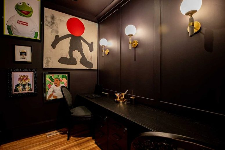 The home office is all dark, with a shared desk, a couple of black chairs and a bright gallery wall