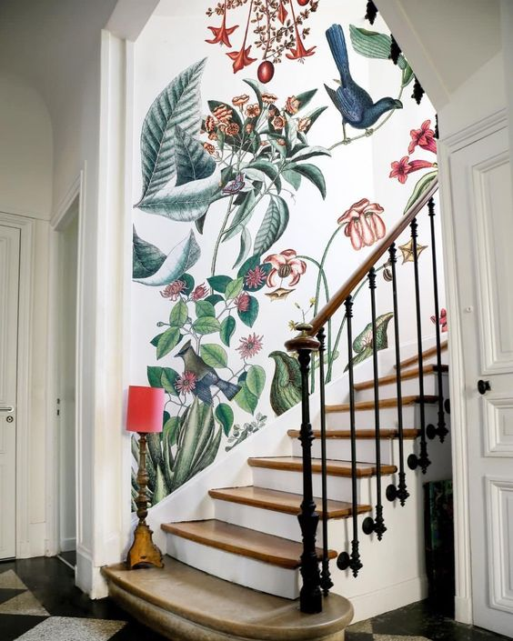 a refined entryway with a beautiful realistic floral accent wall over the staircase looks very chic and sophisticated