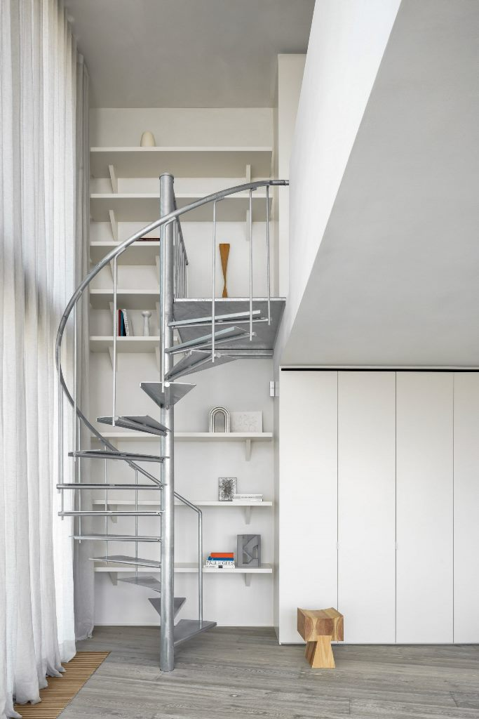 A galvanised-steel staircase connects the apartment's two floors and here you may see white to refresh the space