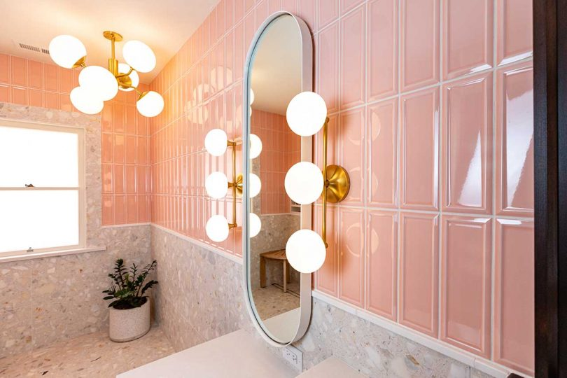 The bathroom is done with pink and terrazzo tiles, with retro lamps and a chandelier and a curved mirror