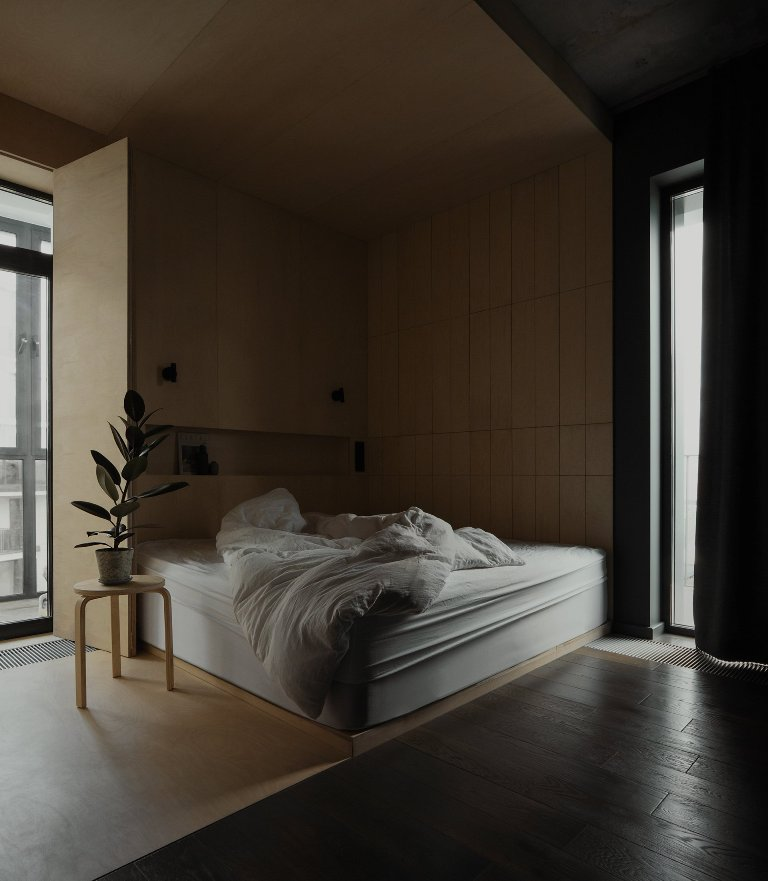 The sleeping zone is clad with light-colored plywood, there's built-in storage and a comfy bed