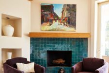 05 a chic and cozy nook with a fireplace clad with glossy blue tiles and purple chairs is a bold space decorated with impeccable taste