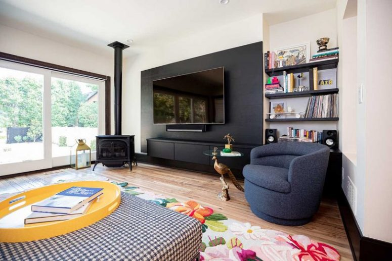 The living room with a glazed wall, which is an access to outdoors, a hearth and colorful pieces is very welcoming