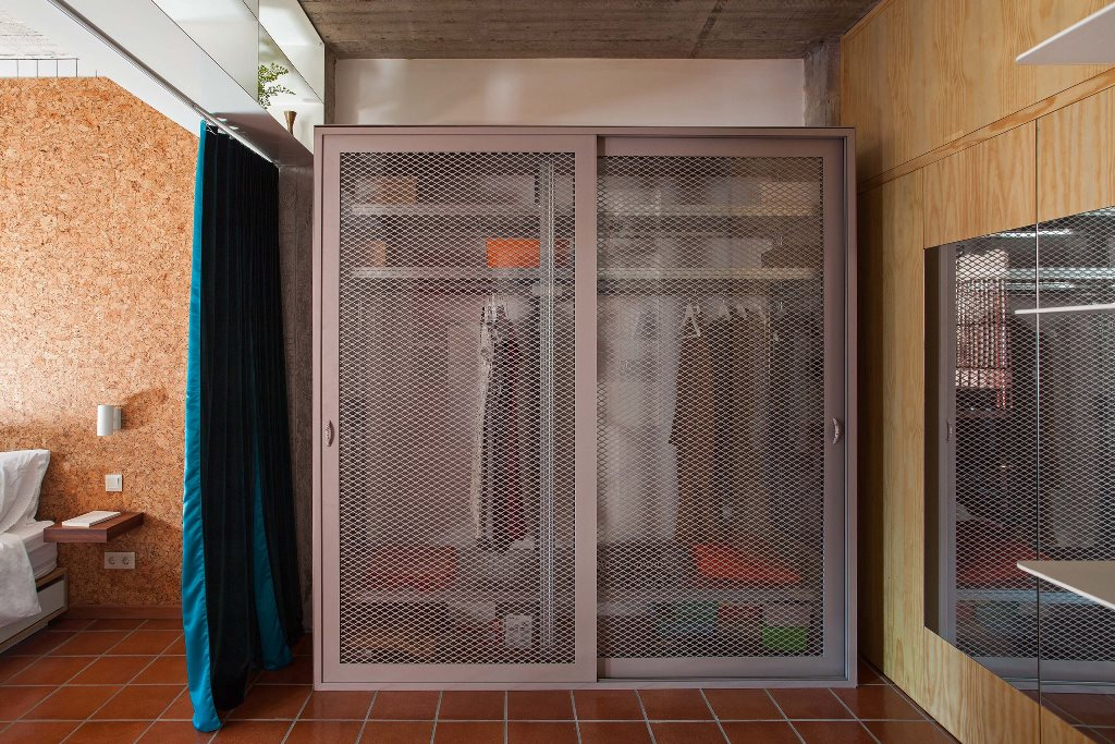 The wardrobe is industrial, with wire doors that are slightly sheer