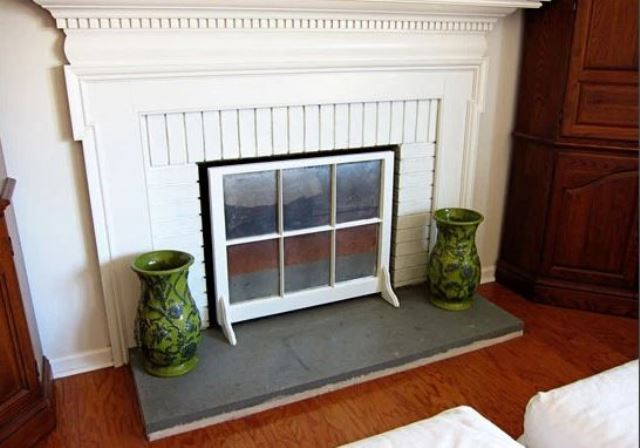 a non-working fireplace cover made of an old window frame is a stylish and very easy idea to go for