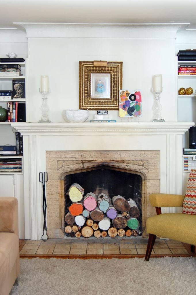 a rustic fireplace with a wooden surround, a white mantel and colorful logs inside is a very whimsical and cool idea