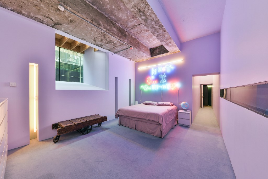 The aster bedroom is pink and lavender, with a neon sign and a rough concrete ceiling