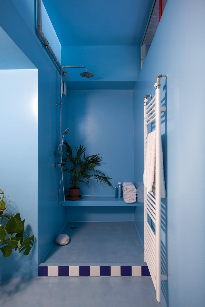 The bathroom is done in light and power blue, with a zoy shower nook and some bright tiles