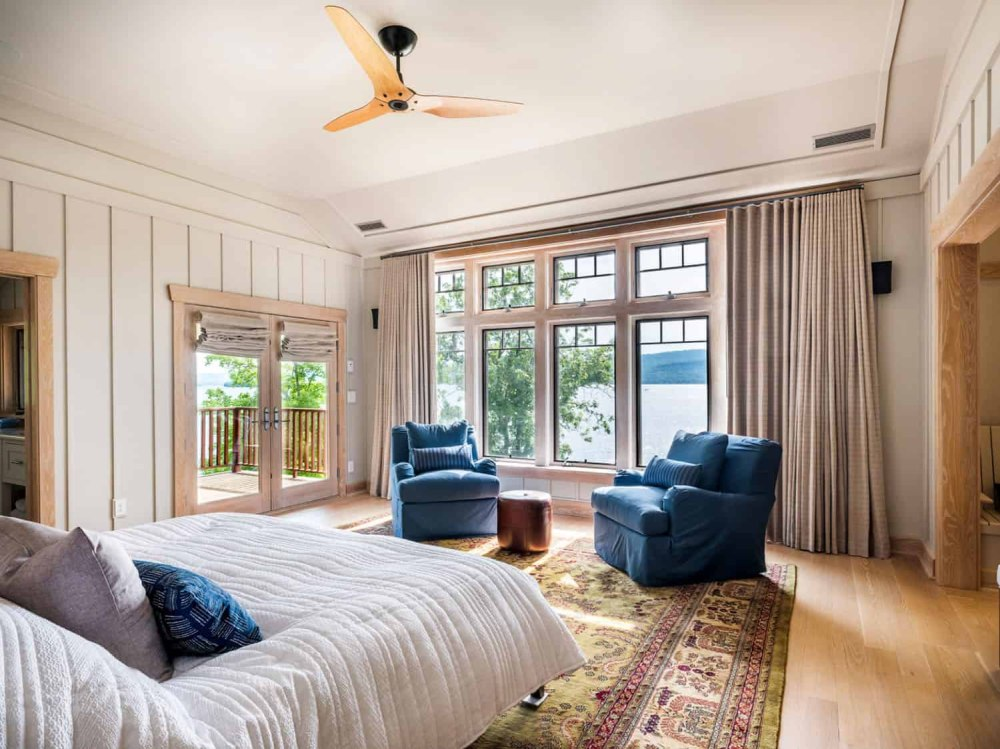 The bedroom is done with blue chairs, a bright boho rug and a comfy bed, the views are stunning