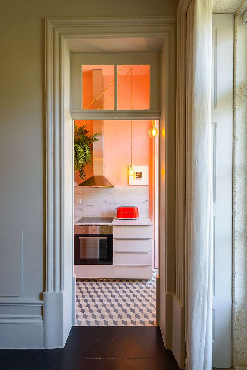 The kitchen shows off white cabinets, a white marble backsplash, peachy walls and greenery and pedant lamps