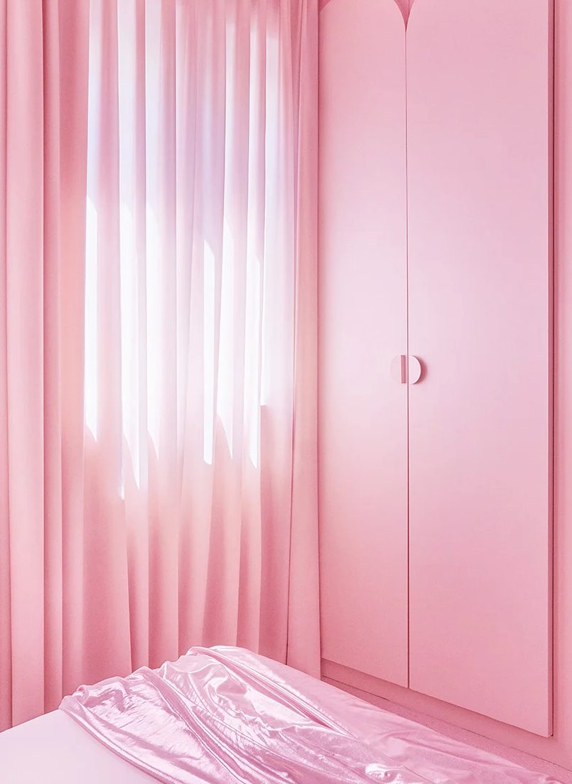 The storage is delicately hidden in the walls and the wardrobe features sleek and simple pink doors