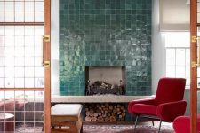 07 a fireplace clad with green glazed tiles and mid-century modern red chairs that infuse the space with color and make it cozy and welcoming