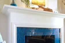 08 a fireplace surrounded with bright blue tiles, with an elegant white mantel and some coastal art on it is ideal for a seaside home
