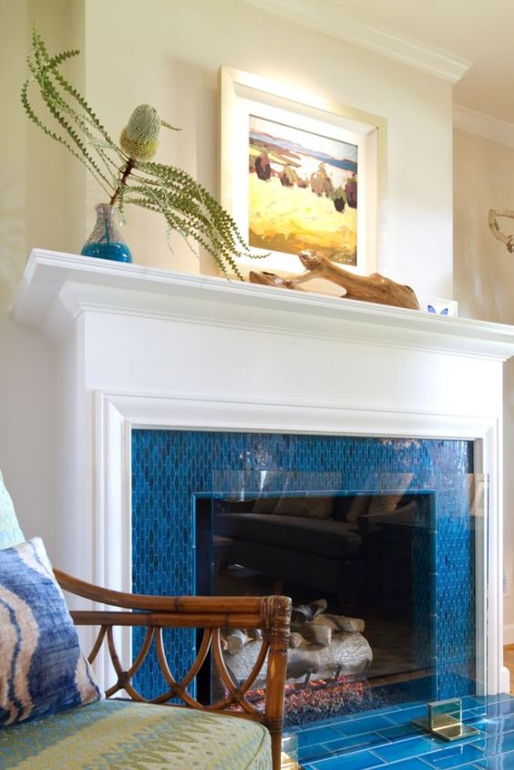 a fireplace surrounded with bright blue tiles, with an elegant white mantel and some coastal art on it is ideal for a seaside home