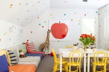 08 a fun and bold kids' playroom with sofas lining up the wall, a creativity zone, polka dot walls and a ceiling and bright toys