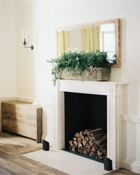 a vintage and refined fireplace with a white mantel and firewood inside plus a planter with greenery and blooms for a chic space