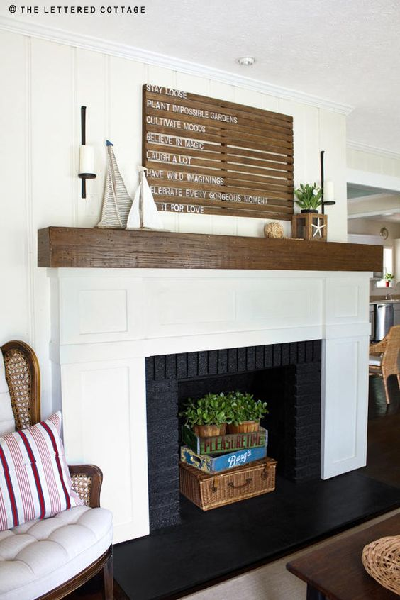 a coastal fireplace with a black and white surround, a stained mantel, a basket, boxes and potted greenery