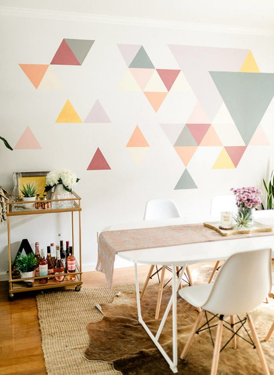 a colorful geometric accent wall done with bright triangles is a creative idea for a modern dining room