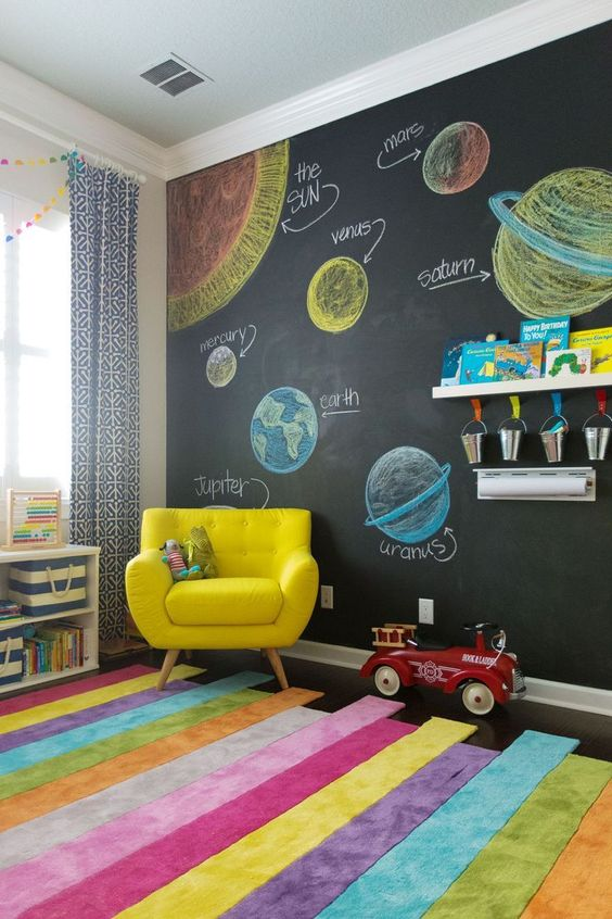 a colorful modern kids' playroom with a chalkboard wall, bold furniture and a rug, colorful crayons and books