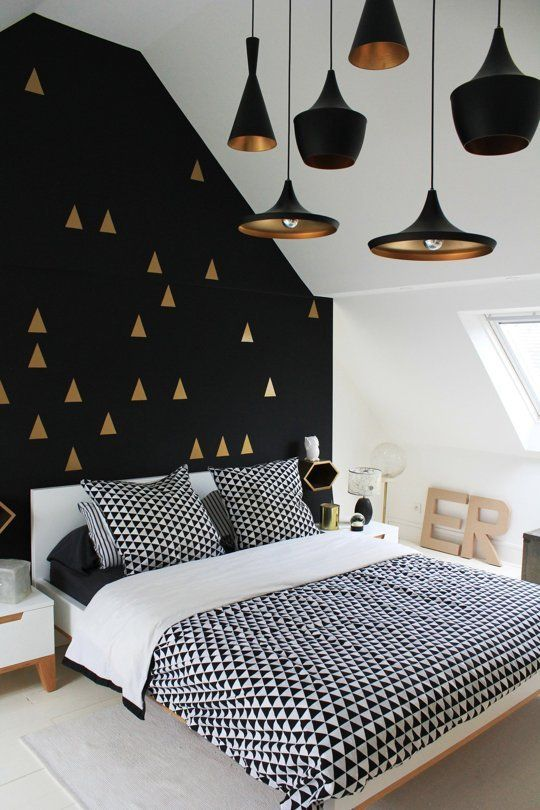 a gorgeous black and gold geometric pattern accent wall plus black and brass pendant lamps that echo with it