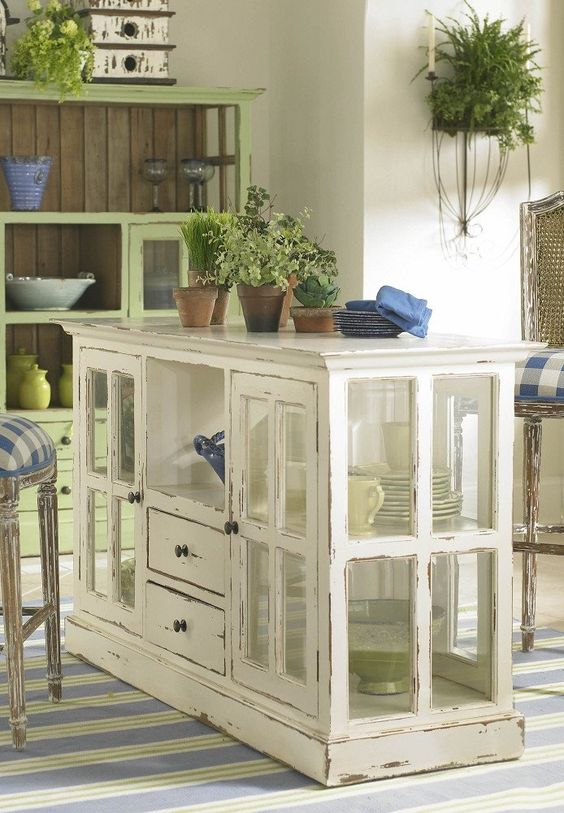 a shabby chic kitchen island made of a cabinet with window frames as glass doors and drawers is a stylish idea