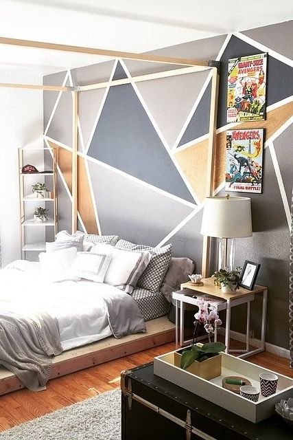 a modern bedroom with a geometric print accent wall, simple furniture and bold posters is a bold idea