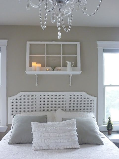 a shelf over the bed made of a shelf and an old window, some candles, a jug and more decor for a vintage white bedroom